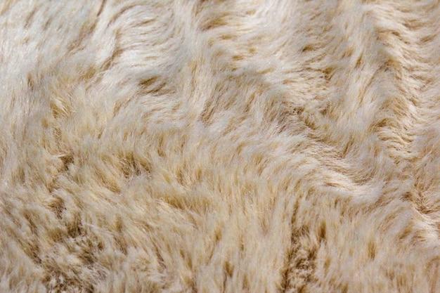 Jasnobiałe miękkie futro z długimi włóknami. białe futro na tle lub tekstury. futrzana, biała, futrzana krata. kudłaty koc tło. puszyste sztuczne futerko tekstylne. płaski świeckich, widok z góry, kopia przestrzeń.