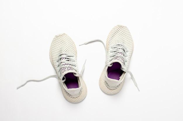 Jasnobiałe trampki do biegania na lekkiej powierzchni. pojęcie biegania, treningu, sportu. . leżał płasko, widok z góry