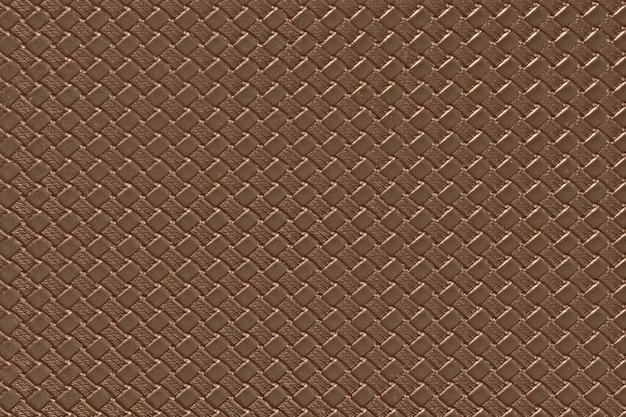 Jasnobrązowe skórzane tło z imitacją splotu tekstury. błyszcząca struktura ze sztucznej skóry.