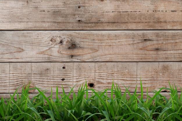Jasnobrązowy drewniany tło z zieloną trawą