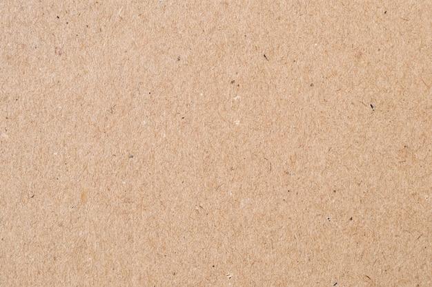 Jasnobrązowy papier pakowy. naturalna powierzchnia arkusza, tło opakowania. tekstura tektury, karton, sztywny papier.