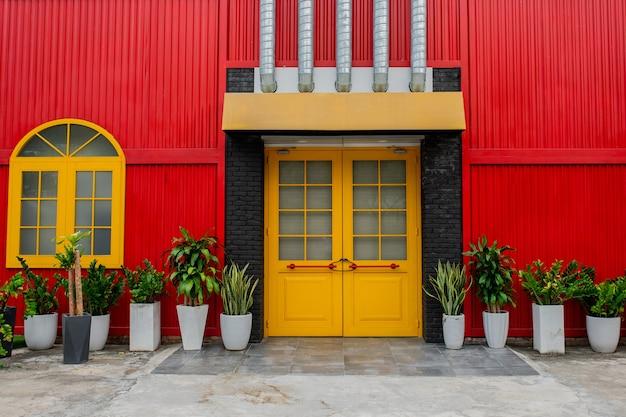 Jasnoczerwony budynek z żółtymi drzwiami i oknem, doniczki z roślinami na tle czerwonej metalowej ściany na miejskiej ulicy w wietnamie, zbliżenie