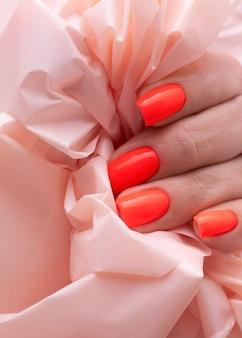 Jasnoczerwony manicure na paznokciach na tle zmięty papier z bliska.