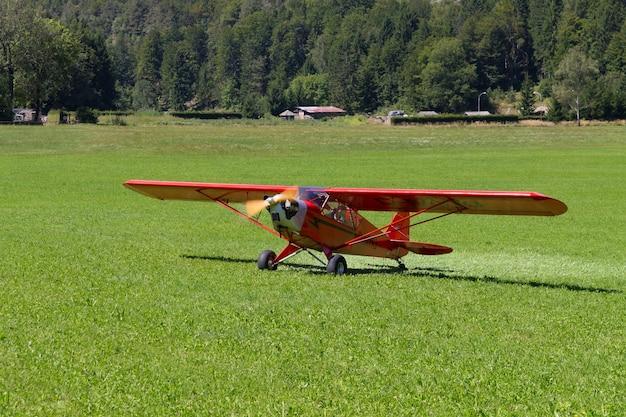 Jasnoczerwony samolot lądujący na zielonej łące, transport, plener