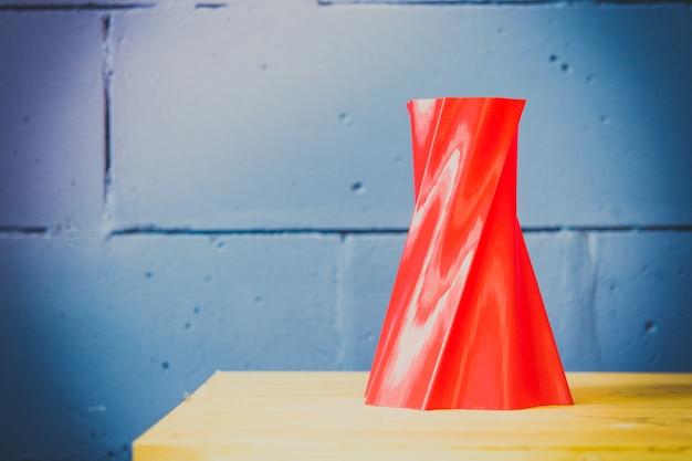 Jasnoczerwony wazon obiektowy wydrukowany przez drukarkę 3d na niebieskiej ścianie z cegły
