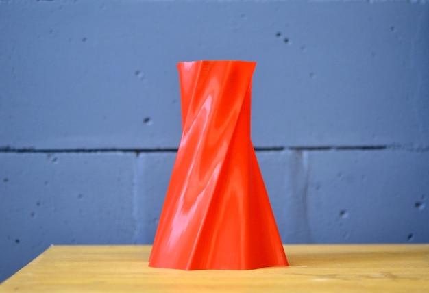 Jasnoczerwony wazon obiektowy wydrukowany przez drukarkę 3d na tle niebieskiego ceglanego muru.