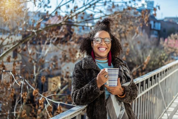 Jasnoniebieski cień do powiek. szeroko uśmiechnięta kręcona dziewczyna z nieostrożną bułeczką na czubku głowy podczas picia herbaty
