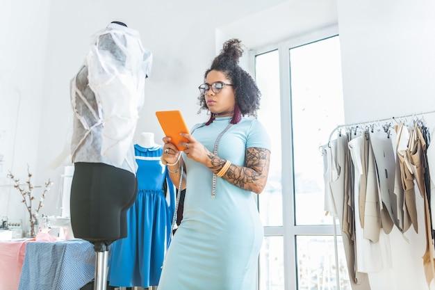 Jasnoniebieski makijaż. młoda dama o krętych kształtach, stojąca w swoim studio z tabletem w pomarańczowej okładce