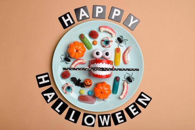 Jasnoniebieski talerz ze słodyczami na pomarańczowym tle z miejscem na tekst. tło dla święta halloween. układ płaski, widok z góry, miejsce do kopiowania. minimalizm halloween