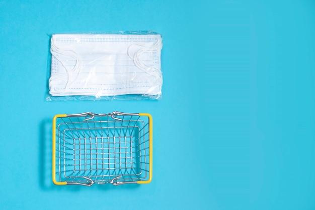 Jasnoniebieskie maski w kieszeni i kosz na zakupy na niebieskiej powierzchni