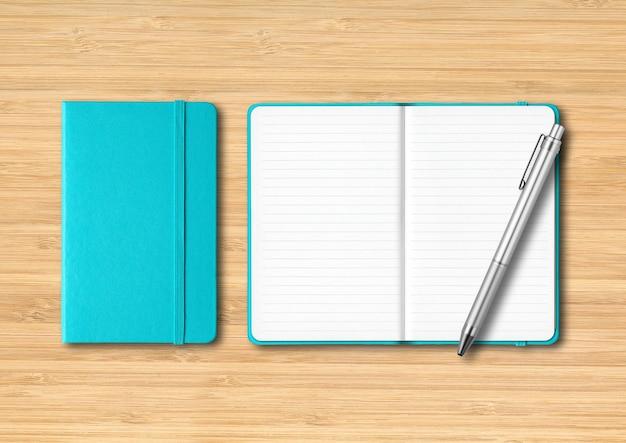Jasnoniebieskie notesy zamykane i otwarte z długopisem. na białym tle na drewniane tła