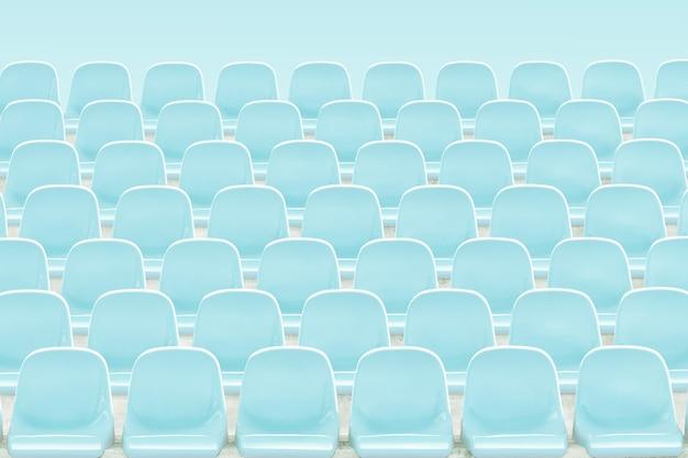 Jasnoniebieskie rzędy siedzeń na stadionie.