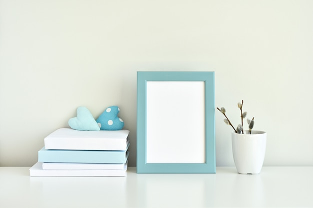 Jasnoniebieskie wnętrze, makieta pustej ramki na zdjęcia, książki, białe i niebieskie dekoracje.