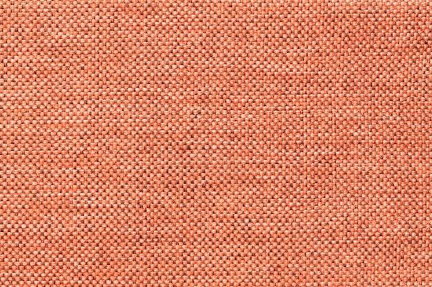 Jasnopomarańczowe tło z gęstej plecionej tkaniny tekstylnej