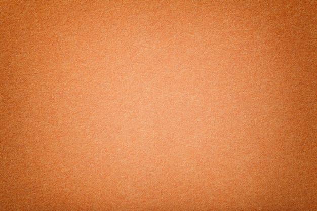Jasnopomarańczowy matowy zamszowy zbliżenie tkaniny. aksamitna faktura filcu.