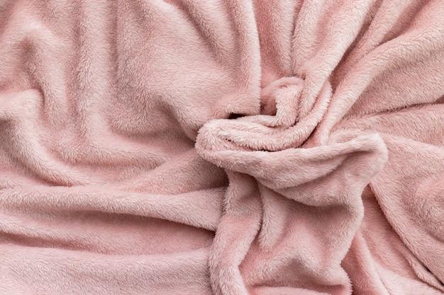 Jasnoróżowa puszysta tekstura tkaniny. koc ze sztucznego futra z pogniecionego materiału tekstylnego.