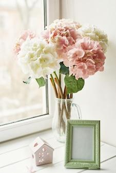 Jasnoróżowe kwiaty hortensji w szklanym wazonie, ramce na zdjęcia i małym drewnianym domku