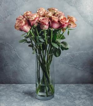 Jasnoróżowy bukiet róż ombre w szklanym wazonie przed szarą ścianą