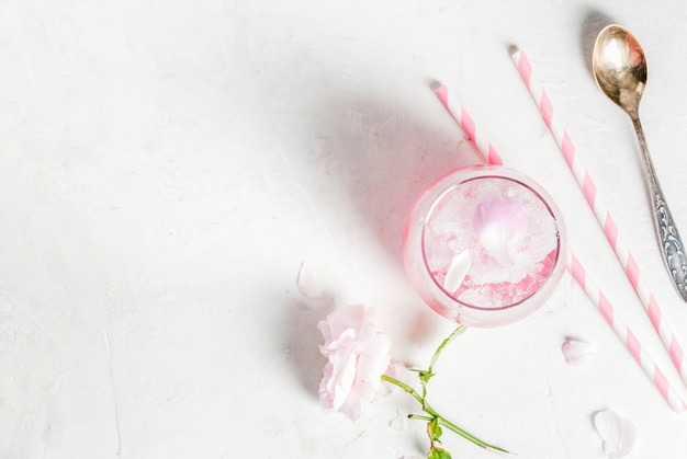 Jasnoróżowy koktajl różany z winem różanym, herbacianymi płatkami róż i cytryną na białym kamiennym betonowym stole.