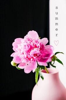 Jasnoróżowy kwiat piwonii w wazonie na czarno białym tle i letnim napisem