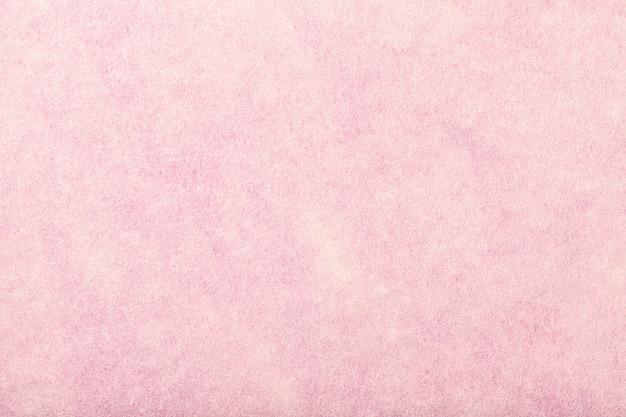 Jasnoróżowy matowy zamszowy zbliżenie tkaniny. aksamitna faktura filcu.