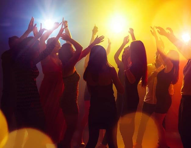 Jasność. tłum ludzi w sylwetce podnosi ręce na parkiecie na neonowym tle. życie nocne, klub, muzyka, taniec, ruch, młodzież. żółto-niebieskie kolory i poruszające dziewczyny i chłopcy.
