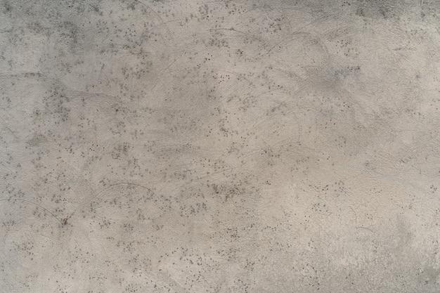 Jasnoszara tekstura z drobnym nakrapianym wzorem. ściana otynkowana. abstrakcyjne tło.