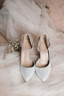Jasnoszare buty dla panny młodej i gałązka łyszczec na białym tiulu.