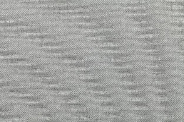 Jasnoszare tło z materiału tekstylnego. materiał o naturalnej fakturze. zasłona.
