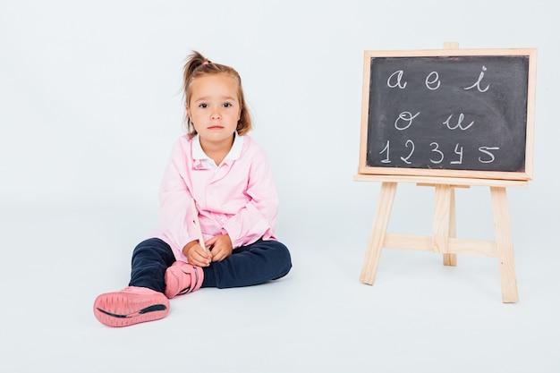 Jasnowłosa dziewczyna ubrana w różowy fartuch dziecięcy w klasie obok tablicy na białej przestrzeni