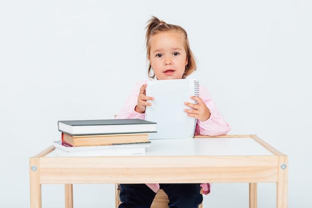 Jasnowłosa dziewczyna w szkole, uśmiechnięta siedzi na krześle obok stołu, trzymając zeszyt, na pustej przestrzeni
