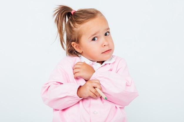 Jasnowłosa dziewczyna w szkole, z ołówkiem w ręku, przestraszona, na białej przestrzeni