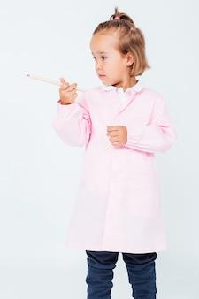 Jasnowłosa dziewczyna z różowym dziecięcym fartuchem i ołówkiem w rękach