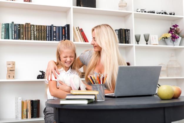 Jasnowłosa kobieta delikatnie przytula swoją córkę podczas pracy przy komputerze. dziewczyna przytula zabawkę