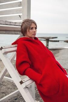 Jasnowłosa kobieta w czerwonym płaszczu, zamyślona, stojąca nad brzegiem morza, wsparta o drewnianą konstrukcję.