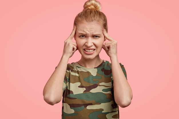 Jasnowłosa młoda kobieta ma sfrustrowany wyraz twarzy, dotyka skroni dwoma palcami wskazującymi, marszczy brwi, ma straszną migrenę, nosi kamuflażową koszulkę, modelki na różowej ścianie