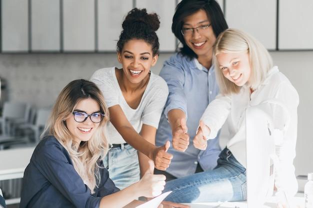 Jasnowłosa specjalistka it wygłupia się z przyjaciółmi, siedzi w miejscu pracy i się śmieje. podekscytowany japoński menedżer pozuje z uśmiechem, stojąc obok blondynki w biurze.