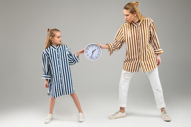Jasnowłose piękne dziewczyny w jasnych koszulach w paski i ciągnące przez okrągły zegar ścienny