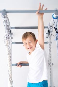 Jasnowłosy chłopak o niebieskich oczach uprawia sport na szwedzkiej ścianie domu kompleksu sportowego
