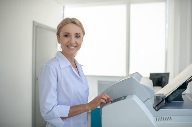 Jasnowłosy młody lekarz patrząc zajęty pracą i uśmiechnięty