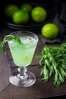 Jasnozielona lemoniada z estragonem i limonką orzeźwiający napój z lodem na czarnym tle