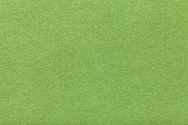 Jasnozielona matowa zamszowa tkanina. aksamitna tekstura odczuwany tło