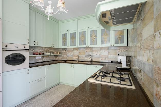 Jasnozielona nowoczesna biała kuchnia czysta aranżacja wnętrza