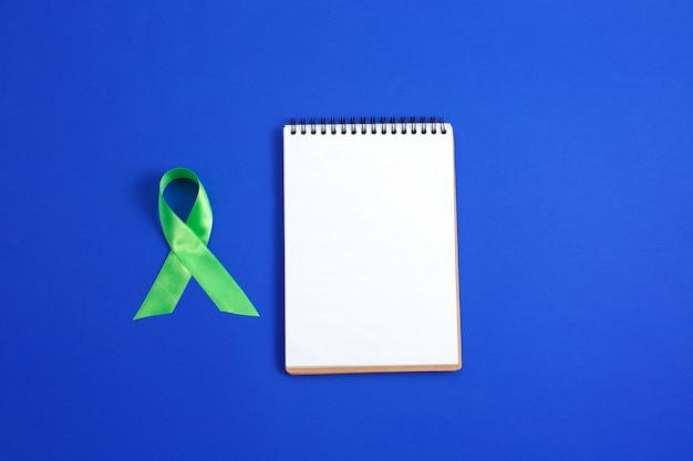 Jasnozielona wstążka i otwarty notatnik. świadomość chłoniaka raka wątroby. pojęcie opieki zdrowotnej i medycyny.