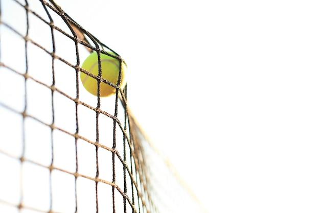 Jasnozielonawożółta piłka tenisowa uderzająca w siatkę.