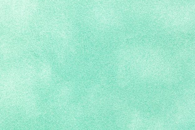 Jasnozielono-cyjanowe matowe tło z zamszowej tkaniny. aksamitna tekstura bezszwowej tkaniny w kolorze niebieskim