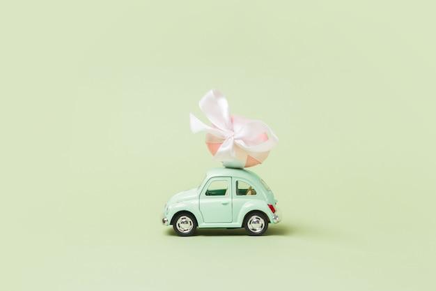 Jasnozielony retro samochodzik niesie jajko wielkanocne