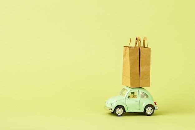 Jasnozielony retro samochodzik-zabawka nosi papierowe torby na zakupy. koncepcja dostawy towarów ekologicznych. darowizna.