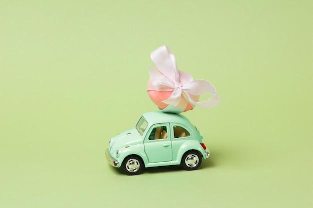 Jasnozielony samochodzik w stylu retro zawiera jajko wielkanocne
