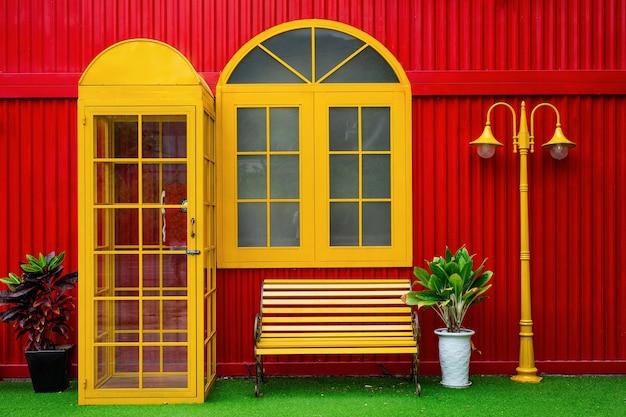 Jasnożółta budka telefoniczna i doniczki z roślinami, ławka i latarnia na tle czerwonej metalowej ściany na ulicy w da nang w wietnamie, zbliżenie